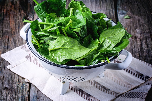 Fresh spinach in metal colander over wooden background