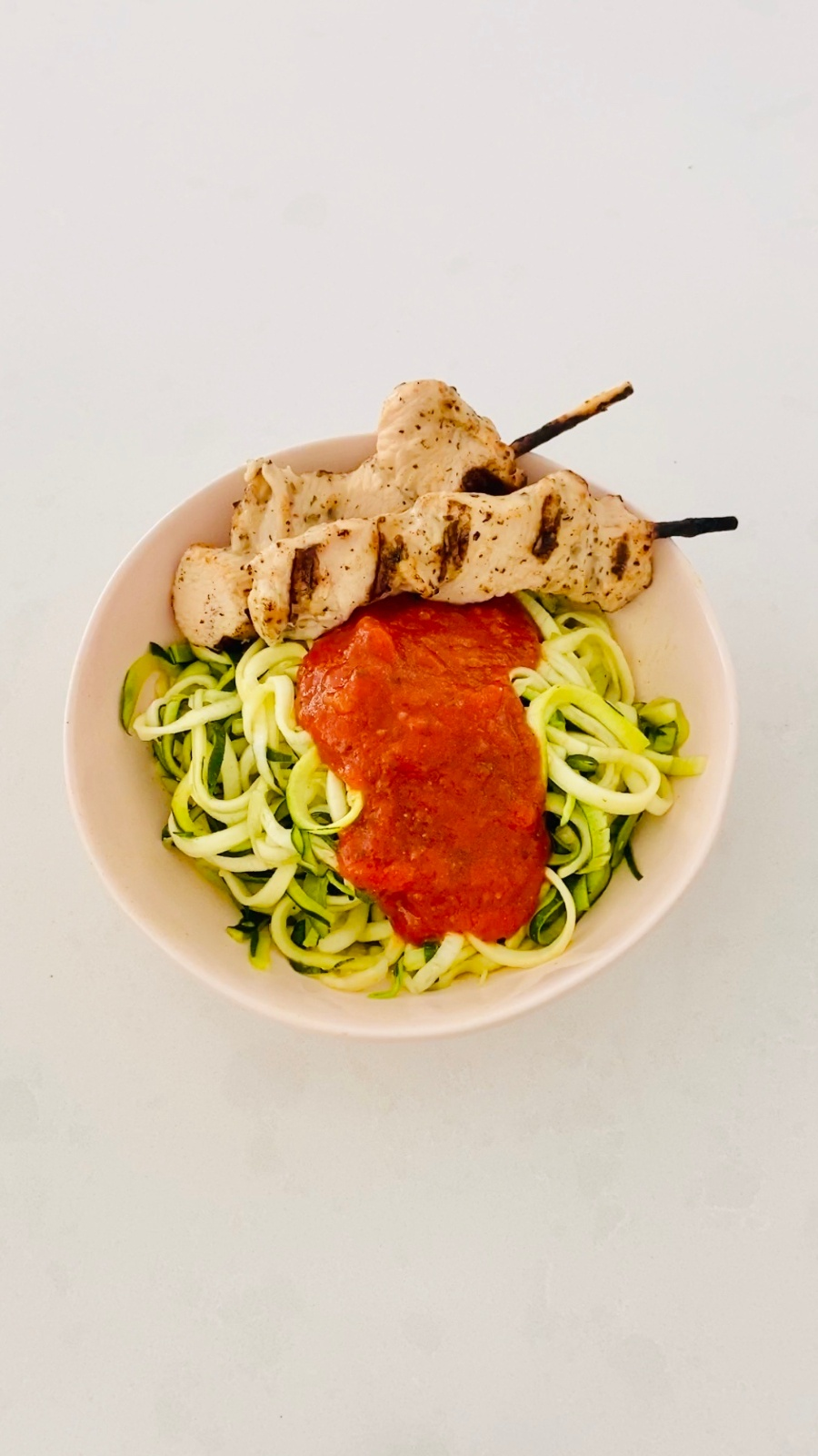 zoodles in white bowl with marinara and grilled chicken on skewer