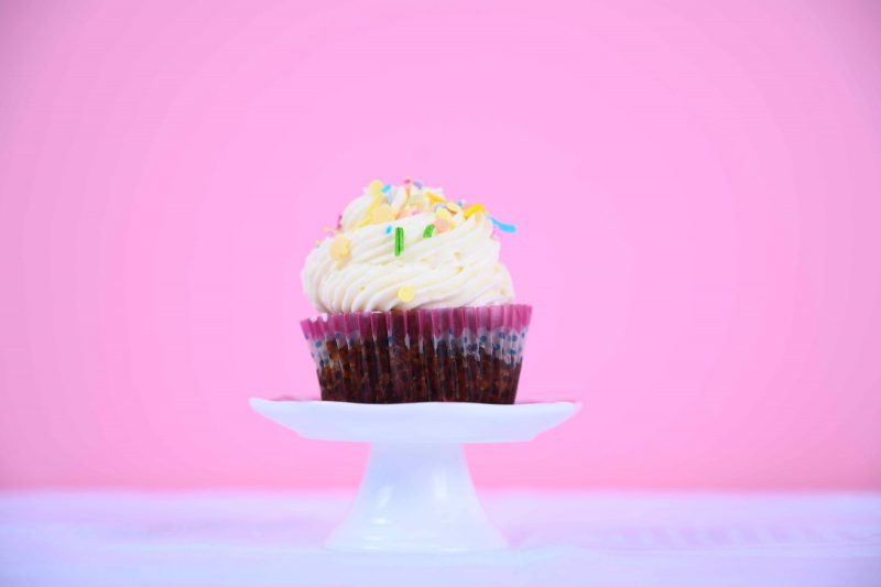 cupcake with vanilla frosting and sprinkles pink background