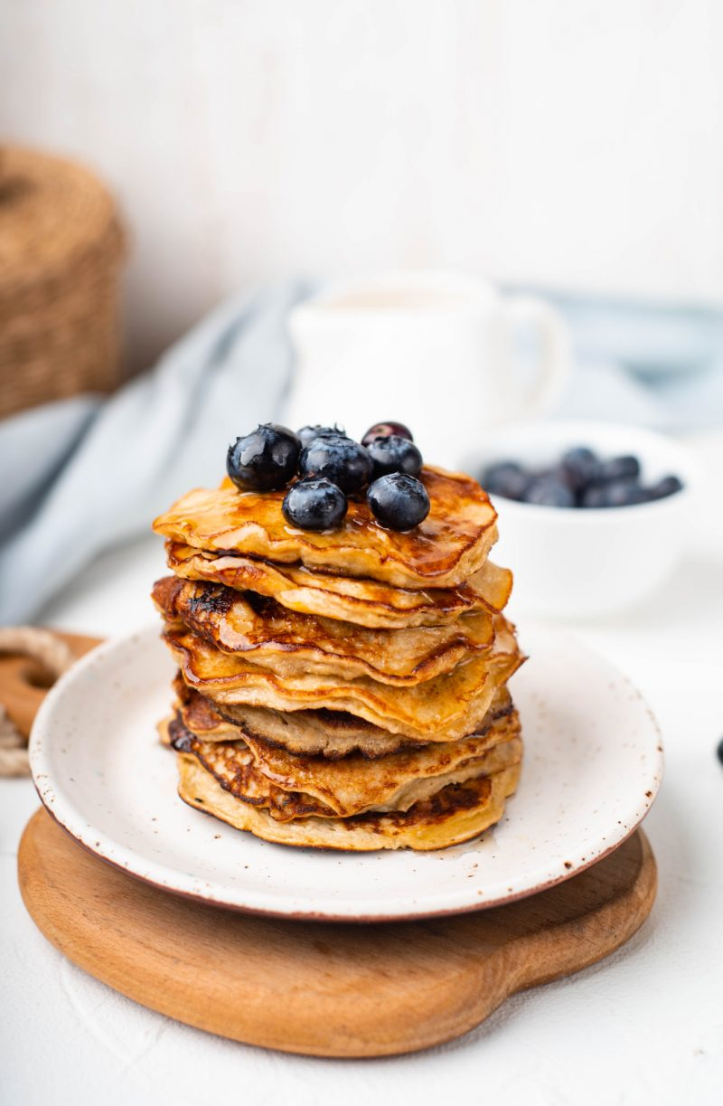 90 day meal plan banana pancakes stacked on a white plate topped with blueberries