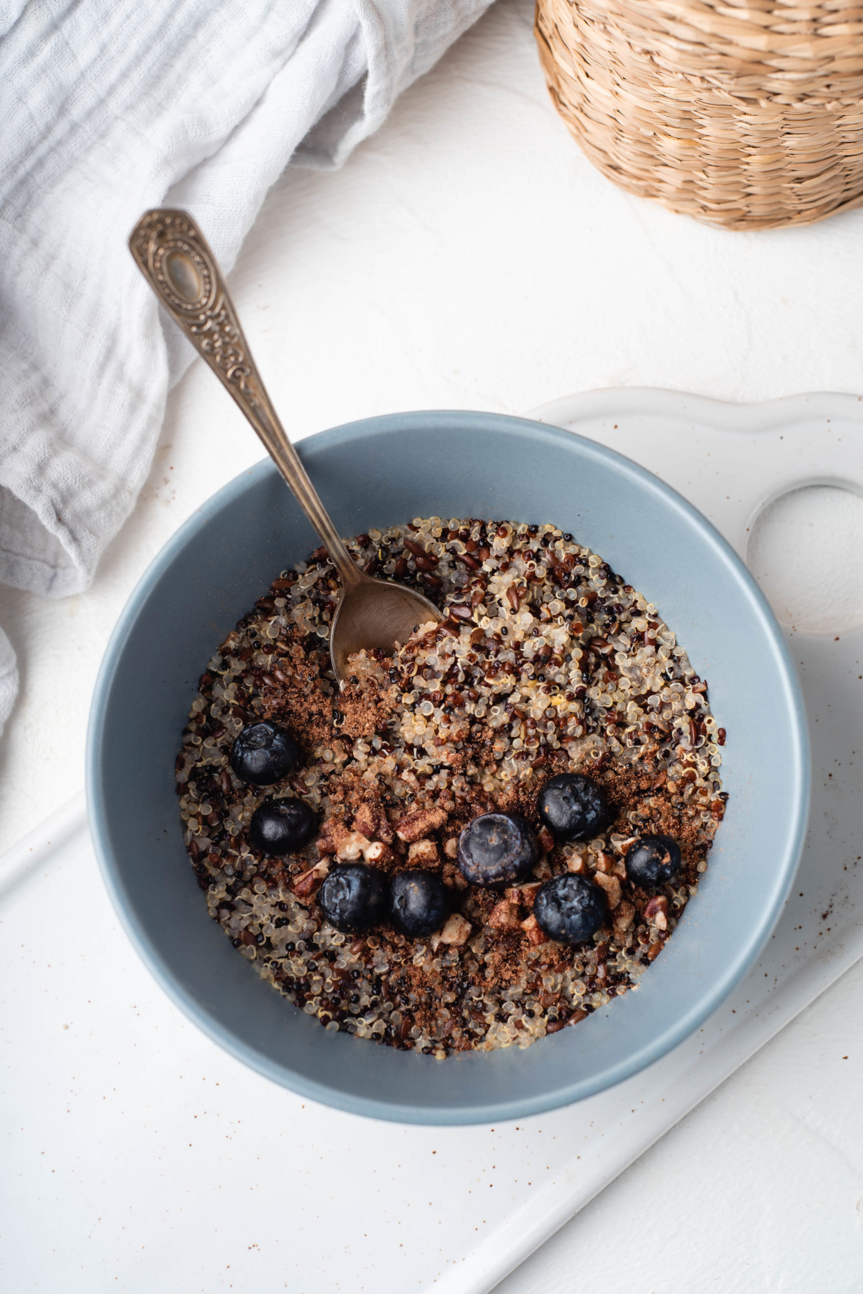 bowl of breakfast quinoa topped with cinnamon and blueberries