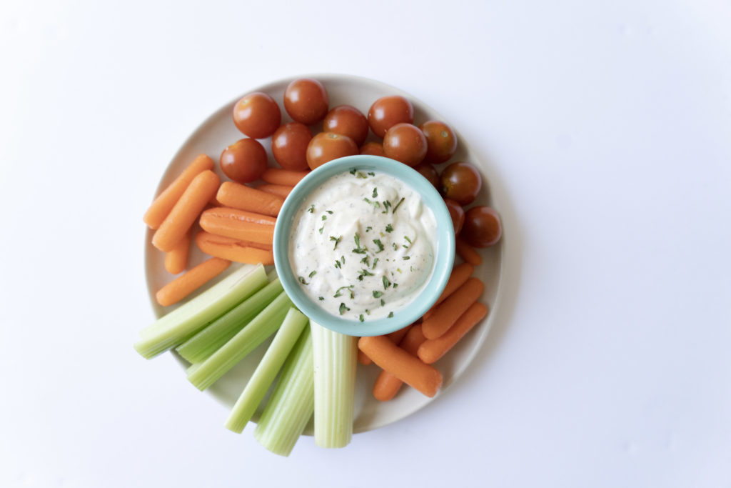 plate with bowl of dairy free ranch with chives served with carrots celery and tomatoes