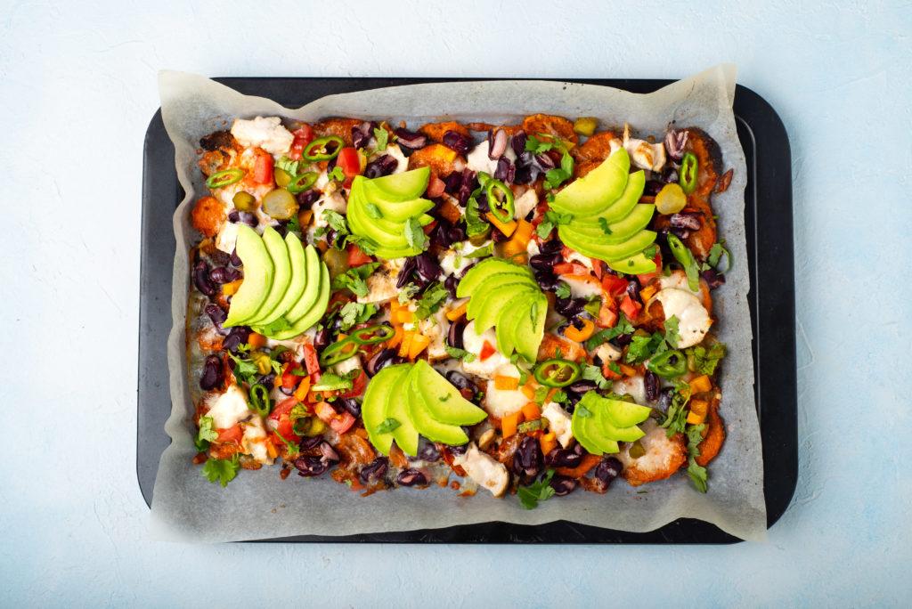 sweet potato nachos topped with beans jalapeno salsa avocado on a sheet pan