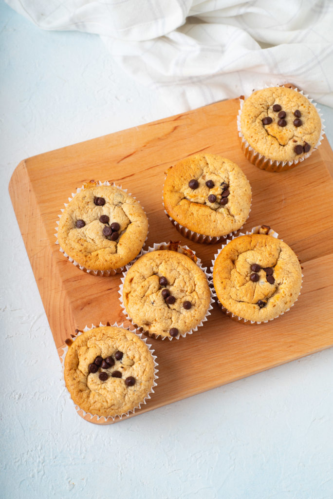 cutting board with batch of flourless blender muffins topped with chocolate chips blogilates